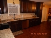 Handscraped Hardwood Floor with Natural Stone Tile and Glass Mosaic Tile Backsplash and Granite Countertop