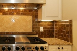 Modern kitchen backsplash with brick tile pattern accented with a ceramic tile panel behind the stove.