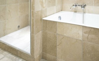 Shower and tub with almond marble tile walls.