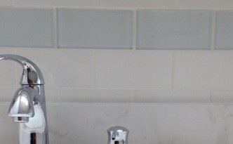Bathroom Remodel with White Ceramic Tile and Glass Tile Accent Strip Faucet Closeup B